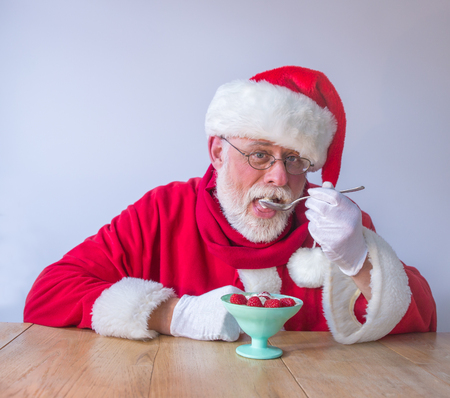 Santa Claus eating Fresh berries with a latge spoon. Close up, white background, copy space