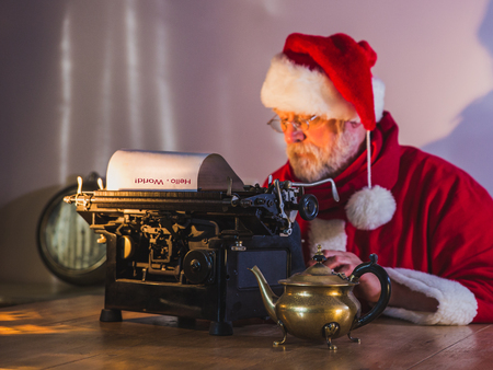 Santa Claus writing a message for people on old typewriter. Santa Claus out of focus, blurry. Foto de archivo