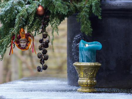 Christmas background of Christmas tree, classic candlestick  standing on snow-covered table in the garden.