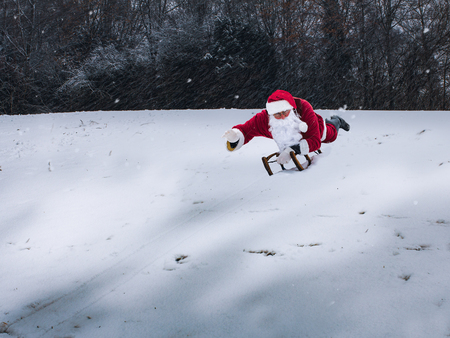 Santa Claus in classic costume riding a sled downhill on a snow covered field. Standard-Bild - 110628699
