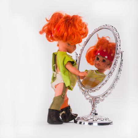 A slovenly little girl watching herself . Doll with red hair looks at herself in the mirror and playing with reflection.