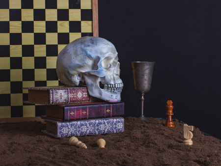 Halloween still life with skull, chess, chess board, books and goblet of wine on a dark background. Stock fotó