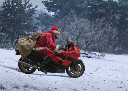 Santa Claus on a red motorcycle with a sack of gifts, drives fast along snow-covered field. 版權商用圖片
