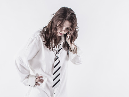 Young business women using smartphone. Brunette long hair. Studio shot on a white background.