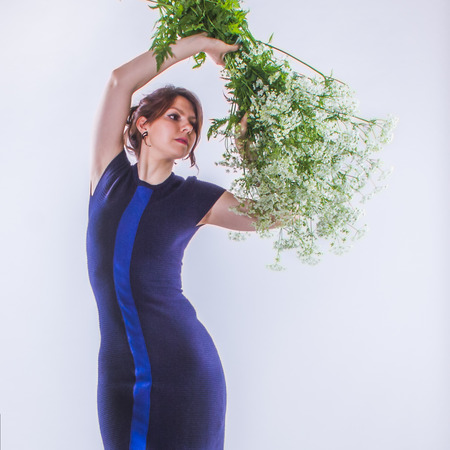 Subtle image of Young charming woman with big bouquet of white elegant flowers. Brunette long hair. Woman posing on white background. Standing in profile.