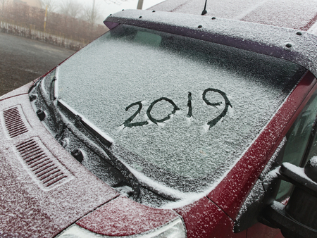 Snow on the  car where the numbers are written 2019, close-up window of the car Stock Photo