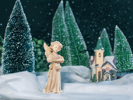 Christmas snowy scene. Decorative statuary of angel sings Christmas songs in the background winter forest and church