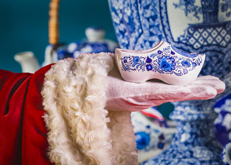 Traditional Dutch Delfts blue decorative wooden shoes in a hands of Santa, close-up, macro photo Stock Photo