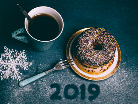 hand drawn 2019 numbers on the dark blue surface covered sugar powder with delicious sweet donuts  and cup of coffee. 免版税图像