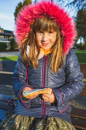 serious little girl with long hair in winter clothes holding sandwich with in her hands. - Image