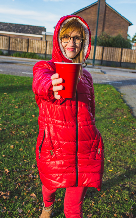 Young smiling blonde girl in red clothes standing on a street and holding red plastic cup in her hands. - Image