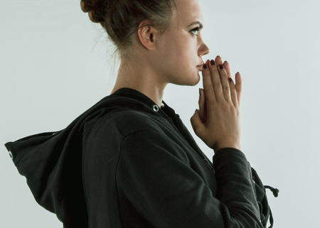 girl pray, address a solemn request or expression of thanks to a deity or other object of worship Фото со стока