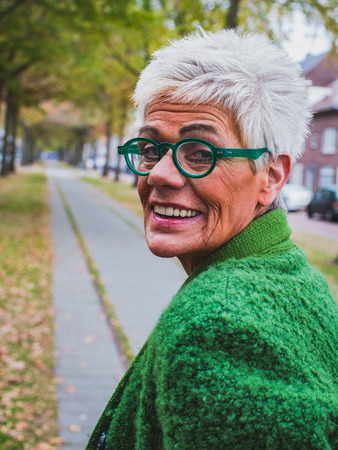 Portrait of an elderly woman of seventy years, looking at the camera and smiling, wandering through the autumn alley of the city Stock Photo
