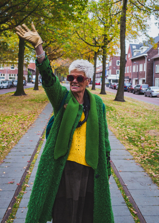 Portrait of a senior friendly woman in green coat walking in the autumn city 스톡 콘텐츠