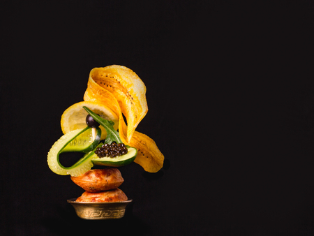 Black caviar with poffertjes, banana chips and cucumber over black background with copy space. Zdjęcie Seryjne