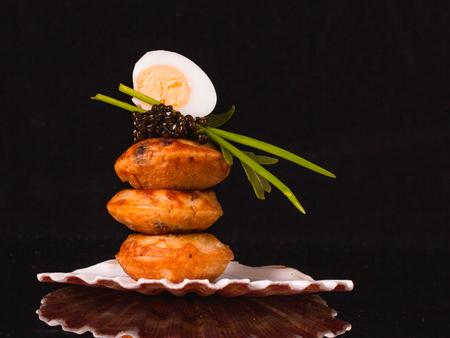 Black caviar with quail egg, poffertjes,rucola, chives over black background with copy space. Zdjęcie Seryjne
