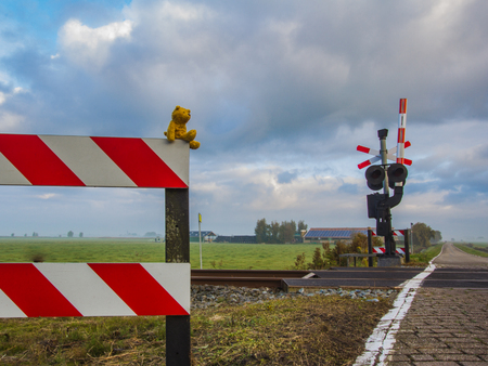 A small soft toy teddy bear is sitting at a railway crossing and looks into the distance with great desire. Stock Photo