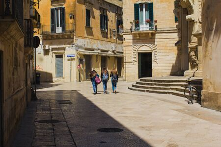 Three unidentified young girls walking Lecce, view from back.