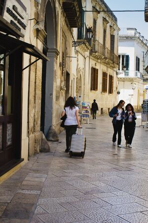 Centre of Lecce. Unidentified two girls looking to smartphone, and one woman walking with suitcase on the street.