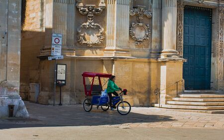 Rickshaw girl working on the square near history cathedral located in the city center of Lecce, northern front.