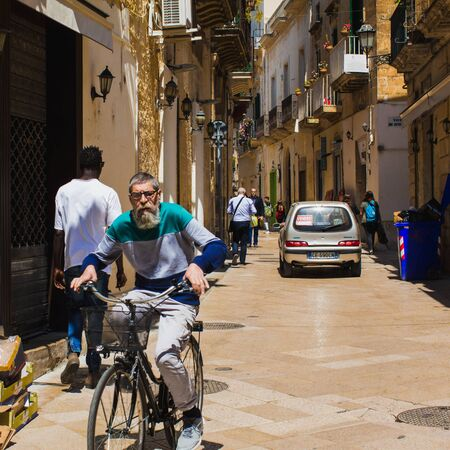 Old men ride bicycle on the street of Lecce, daily real modern life in historic town.