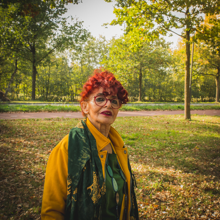 Eastern older woman wear bright clothes in the sunny day of autumn, walks in nature, outdoor, Europe.