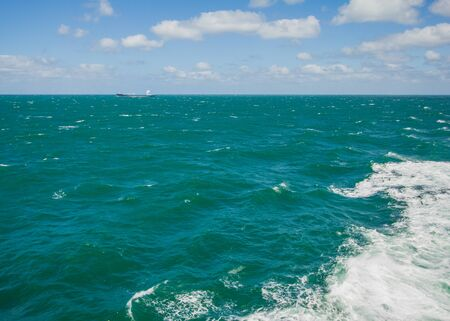 magnificent open space of the turquoise sea, horizon line with a ship in the big distance