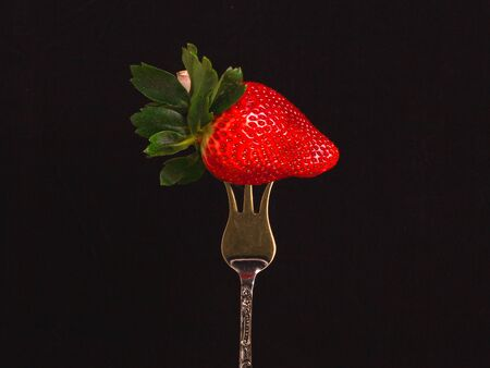 Big red ripe strawberry on a silver dessert fork on the black background with copy space