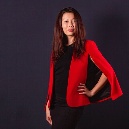 Beautiful Asian business woman in a elegant red jacket on a black background Stock fotó