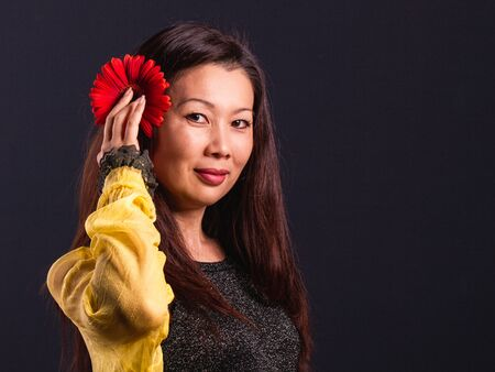 Middle aged Asian beautiful happy woman looking at camera.