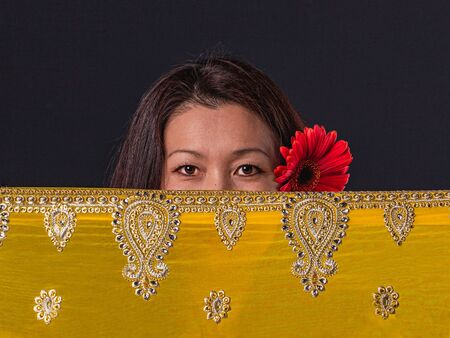 Portrait of middle-aged Asian beautiful women, closed face with yellow silk with traditional Asian patterns. , front view. Stock fotó