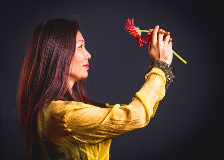 Close up of middle aged asian women with red flower in yellow silk blouse on dark background.