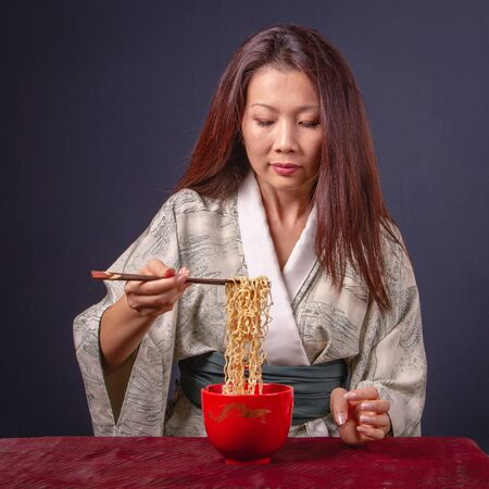 Beautiful Asian woman with long hair in kimono eating noodle with wooden chopsticks. Front view, close-up, on a dark background.