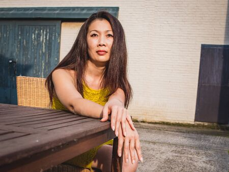 Asian model of average age in a yellow festive dress sits against the background of a white brick wall, outdoor, Industrial space, in the evening sunlight. Фото со стока