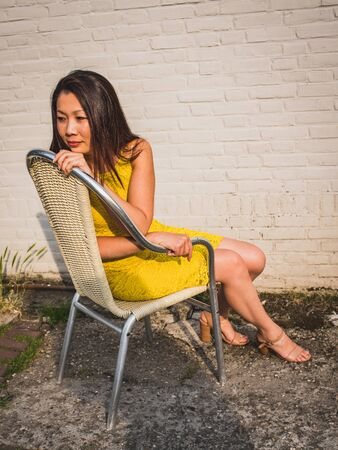 Asian model of average age in a yellow laco dress sits against the background of a white brick wall, outdoor, view from above.