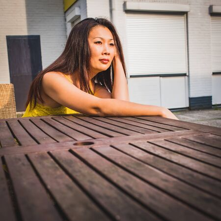 Asian model of average age sits against the background of a white brick wall, outdoor, Industrial terrain, in the sunlight. Imagens