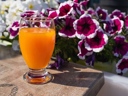 full glas of orange juice on the table, outdoor, sunny morning 写真素材