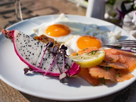 great tasteful summer breakfast with fried eggs, salmon and fresh drakenfruit (also known as cactus fruit, prickly pear, cactus fig, and tuna)