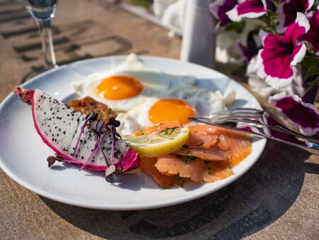 Exotic summer breakfast with fried eggs, salmon and fresh drakenfruit outdoor,  in hotel