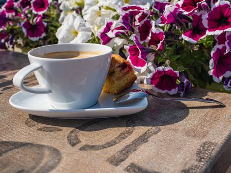 cup of coffee on the table, sunny morning in the garden, outdoor, hotel
