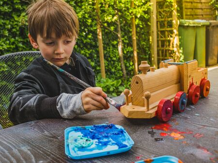 Small child, boy of 6 years, colors homemade train with brush in the garden. Colorful wooden toy. Banco de Imagens