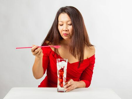 Asian beautiful woman wearing red dress eats tasty strawberry fruit dessert, white table on a white background, front view. Stock Photo
