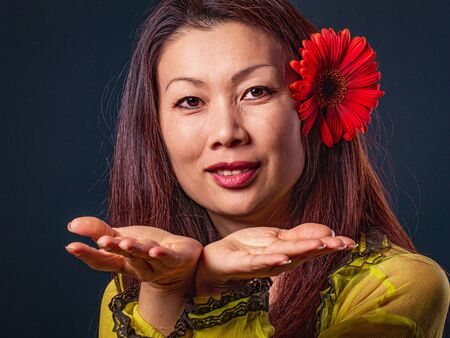 Portrait of middle aged Asian beautiful happy woman, looking at camera and making a hand gesture.