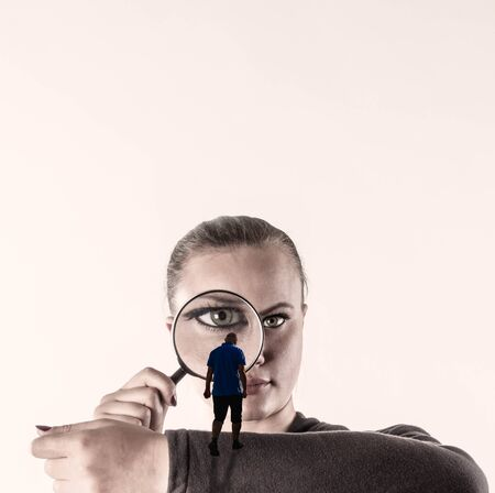 A woman looks at a man intently and with curiosity looks through a magnifying glass.