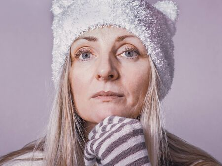 Image of pensive middle-aged lady with gray eyes dressed in winter clothes in pastel colors, posing looking at the camera.