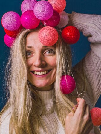Portrait of a joyful holding decorative bright colored round lamps on her head. Preparing for the holiday with a joke.