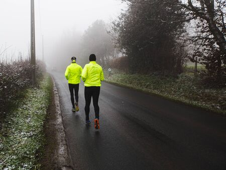 Two athletic young man running in the winter nature. 写真素材