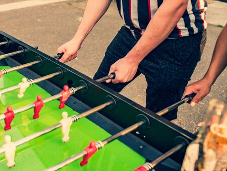 People playing table football outdoor, summer holiday.