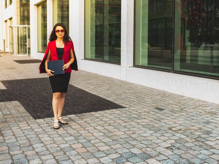 Asian  beautiful business woman in red elegant suit and red sunglasses walking against modern office building. 写真素材