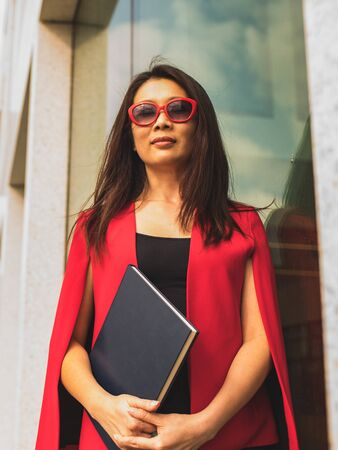 Happy Asian brunette in a red suit and sunglasses  against a modern building dreams of new plans.